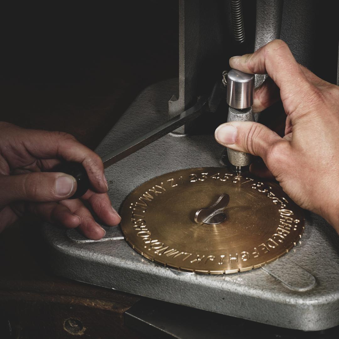Zwei Hände an einer Gravurmaschine in der Goldschmiedewerkstatt