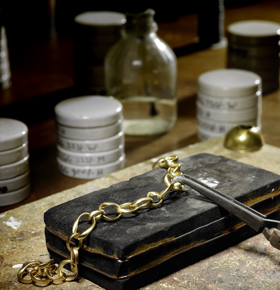 Goldene Kette auf einem Stück Kohle in Goldschmiedewerkstatt